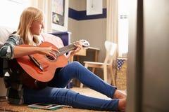 Flicka som spelar gitarren i hennes sovrum Arkivbild