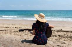 Flicka som spelar gitarren p? stranden royaltyfri bild