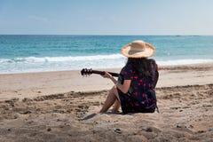 Flicka som spelar gitarren p? stranden royaltyfria bilder