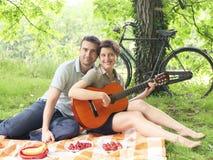 Flicka som spelar gitarren under en pic-nic Arkivfoto