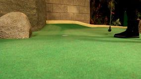 Flicka som spelar golf inomhus stock video