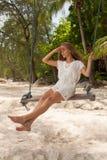 Flicka som spelar gungan på stranden Royaltyfria Foton