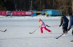 Flicka som spelar hockey på is Royaltyfri Fotografi