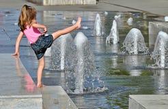 Flicka som spelar i en springbrunn Arkivfoton