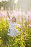 Flicka som spelar i ett fält av blommor Royaltyfria Foton