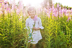 Flicka som spelar i ett fält av blommor Arkivbilder