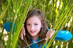 Flicka som spelar i naturen som kikar från gröna rottingar Arkivbild