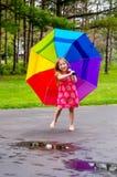 Flicka som spelar i pölar med paraplyet Fotografering för Bildbyråer