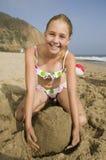 Flicka som spelar i sand på stranden arkivfoton