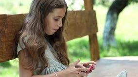Flicka som spelar leken på hans smartphone arkivfilmer