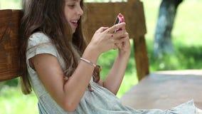 Flicka som spelar leken på hans smartphone stock video