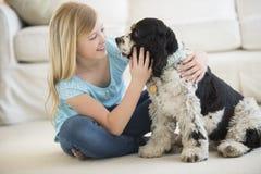 Flicka som spelar med den älsklings- hunden i vardagsrum Royaltyfri Foto