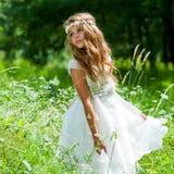 Flicka som spelar med den vita klänningen i fält. Royaltyfri Foto