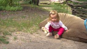 Flicka som spelar med dockan på jordning arkivfilmer