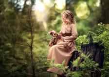 Flicka som spelar med en levande uggla arkivfoton