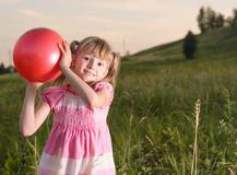Flicka som spelar med en röd boll i parkera Royaltyfri Fotografi