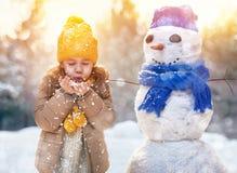 Flicka som spelar med en snögubbe Arkivfoto