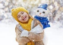 Flicka som spelar med en snögubbe Royaltyfri Fotografi