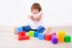 Flicka som spelar med färgrika kuber royaltyfri bild