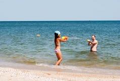 Flicka som spelar med farsan på stranden Royaltyfria Foton