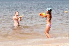 Flicka som spelar med farsan på stranden Arkivfoto