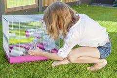 Flicka som spelar med hamstern i bur Royaltyfria Foton