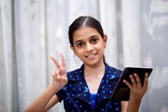 Flicka som spelar med hennes flik Arkivbild