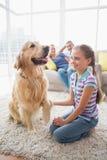 Flicka som spelar med hunden medan föräldrar som hemma kopplar av Arkivfoton