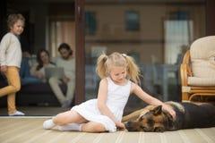 Flicka som spelar med hunden utanför, familjinsidahus på bakgrund arkivbild