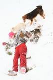 Flicka som spelar med hundkapplöpning i snö Arkivfoton