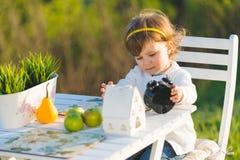 Flicka som spelar med klockan Royaltyfria Foton