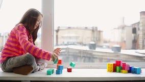 Flicka som spelar med leksaken för byggnadskvarter stock video