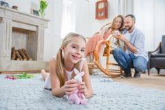 Flicka som spelar med leksakkanin Arkivbild