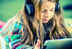 Flicka som spelar med minnestavlan arkivfoto