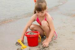Flicka som spelar med sand på havskusten royaltyfria foton