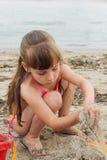 Flicka som spelar med sand på havskusten royaltyfri fotografi
