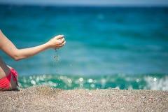 Flicka som spelar med sand på stranden arkivbild