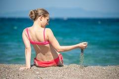 Flicka som spelar med sand på stranden Royaltyfri Fotografi