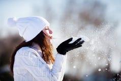 Flicka som spelar med snö Arkivbild