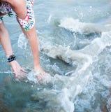 Flicka som spelar med vatten i havet royaltyfria bilder