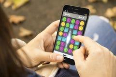 Flicka som spelar mobilleken Royaltyfri Bild
