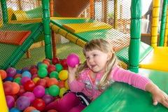 Flicka som spelar och har en bra tid i ett bollrum på lekplatsen royaltyfri fotografi