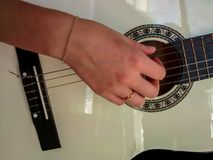 Flicka som spelar på den vita klassiska gitarren Royaltyfri Foto