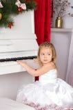 Flicka som spelar på det vita pianot royaltyfria bilder