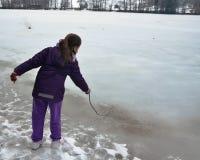 Flicka som spelar på en djupfryst sjö Royaltyfri Foto