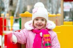 Flicka som spelar på en lekplats för barn` s i vinter arkivbild