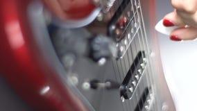 Flicka som spelar på en röd elektrisk gitarr arkivfilmer