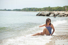 Flicka som spelar på en stenig strand Arkivbilder