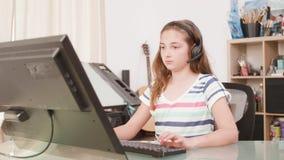 Flicka som spelar på hennes dator ett online spel med hennes faktiska vänner arkivfilmer