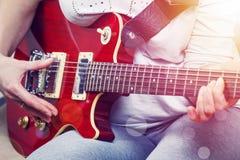 Flicka som spelar på röd närbild för elektrisk gitarr Arkivbild